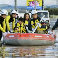 Emergency workers rescue residents in a flooded residential area in Iwaki, Fukushima Prefecture. | KYODO