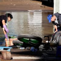 Clean-up begins in a flooded residential area in Kawasaki. | REUTERS
