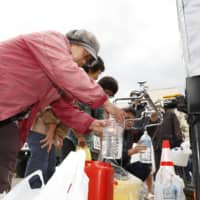 People in the town of Marumori, Miyagi Prefecture, collect water supplies on Tuesday after the entire neighborhood was flooded and homes had their water cut off following Typhoon Hagibis. | KYODO