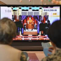 People watch the live broadcast of Emperor Naruhito's enthronement ceremony Tuesday at an evacuation center in Motomiya, Fukushima Prefecture. | KYODO