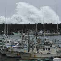 Surging waves hit against the breakwater behind fishing boats as Typhoon Hagibis approaches at the port in the town of Kiho, Mie Prefecture on Saturday. | AP