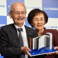 Akira Yoshino, a winner of the 2019 Nobel Prize in chemistry, and his wife, Kumiko, hold a model of a lithium-ion battery during a news conference Thursday in Tokyo. | SATOKO KAWASAKI
