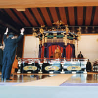 Like father, like son: Prime Minister Toshiki Kaifu leads a cheer of 'banzai' during the Ceremony of Accession for Emperor Akihito in 1990. The emperor and empress sit on the takamikura and michōdai, respectively. | AFP-JIJI