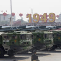 Military vehicles carrying DF-17 hypersonic missiles take part in a parade to commemorate the 70th anniversary of the founding of the People's Republic of China in Beijing on Tuesday. | AP