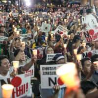 Protesters in Seoul hold placards on Aug. 3 reading 'No Abe!' during a demonstration against Japan's removal of South Korea from a list of trusted trading partners. | BLOOMBERG
