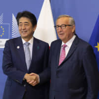 Prime Minister Shinzo Abe is greeted by European Commission President Jean-Claude Juncker prior to a meeting at EU headquarters in Brussels on Sept. 27. The new Japan-EU agreement is an important move in the right direction to meet China's international challenges. | AP