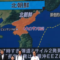 A big screen in Tokyo shows a news report on North Korea's two missile launches into the sea Wednesday, a day after Washington and Pyongyang announced they would resume stalled nuclear talks later this week. | AFP-JIJI