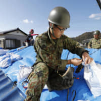 Members of the Ground Self-Defense Forces make an emergency repair on a roof in Kyonan, Chiba Prefecture, on Sept. 15. Typhoon Faxai damaged at least 20,000 houses in Chiba last month,  and caused extensive power outages and disruptions to water supplies. | KYODO