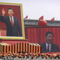 Participants in Beijing on Tuesday cheer beneath a large portrait of Chinese President Xi Jinping during a parade to commemorate the 70th anniversary of the founding of  the People's Republic  of China and showcasing the nation's ambition as a rising global force. | AP