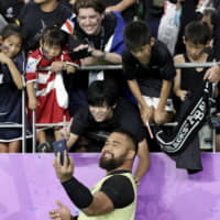 New Zealand's Nepo Laulala poses for a selfie with fans after the All Blacks' win over Canada on Wednesday in Oita. | AP