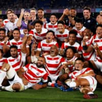 Japan's players pose for a group photo after winning their Rugby World Cup Pool A match against Scotland in Yokohama on Sunday. | AFP-JIJI