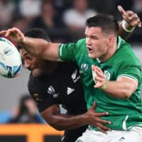 New Zealand's Sevu Reece (left) and Ireland's Jonathan Sexton fight for the ball in Saturday's match. | AFP-JIJI