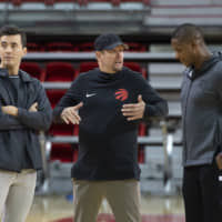 Toronto Raptors head coach Nick Nurse (center) gestures while talking to team president Masai Ujiri (right) as general manager Bobby Webster looks on during an Oct. 1 practice session at Laval University in Quebec City, Quebec. | AP
