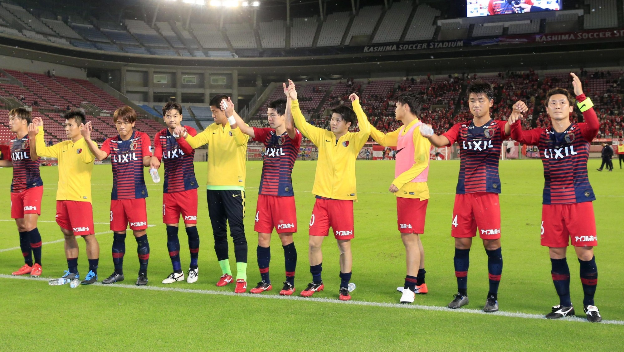 Antlers players salute fans at Kashima Stadium after defeating Honda FC on Wednesday in the quarterfinals of the Emperor's Cup.   KYODO