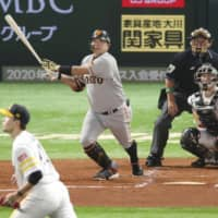 The Giants' Shinnosuke Abe whacks a solo homer in the second inning on Saturday.   KYODO