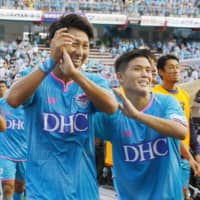 Sagan Tosu's Yohei Toyoda (left) and Takashi Kanai celebrate after the team's 2-1 home victory over FC Tokyo on Saturday. | KYODO