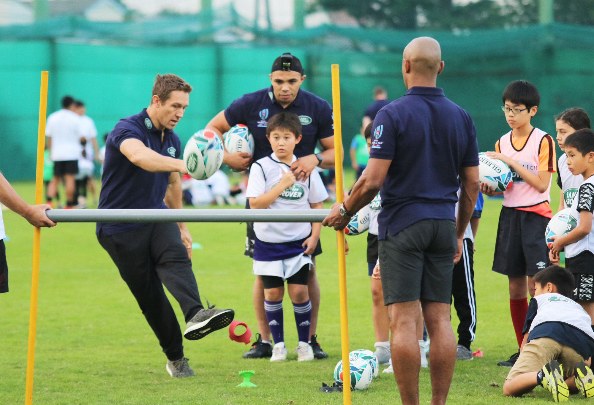 Former England flyhalf Jonny Wilkinson demonstrates kicking technique, while ex-South African winger Bryan Habana (center) looks on at Monday's 'Rugby Introduction Days' event in Tokyo. | KAZ NAGATSUKA
