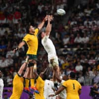 Australia's Rory Arnold (left) and England's Tom Curry fight for the ball during a lineout on Saturday at Oita Stadium. | AFP-JIJI