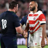 Japan captain Michael Leitch (right) shakes hands with Scotland prop Zander Fagerson after their Rugby World Cup Pool A match on Sunday in Yokohama. | AFP-JIJI