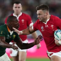 Wales flyhalf  Dan Biggar (right) tries to elude South Africa's Makazole Mapimpi during their Rugby World Cup semifinal on Sunday in Yokohama.  | AFP-JIJI