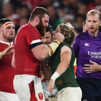 Wales lock Jake Ball (left) tussles with South Africa's Faf de Klerk during their semifinal match on Sunday. | AFP-JIJI