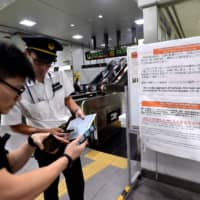 Aaron Tan, from Singapore, receives help from a Hamamatsu Station staff member next to a travel warning sign regarding Typhoon Hagibis on Thursday. | REUTERS