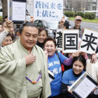 Sokokurai poses with supporters in March 2013 after a Tokyo District Court ruling invalidating his expulsion from the Japan Sumo Association for match-fixing. Sokokurai returned to action in that year's Nagoya Basho and acquired Japanese citizenship last month. | KYODO