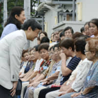 Crown Prince Naruhito and Crown Princess Masako speak with individuals affected by the 2011 Great East Japan Earthquake and tsunami at a temporary housing facility in Shichigahama, Miyagi Prefecture, on Aug. 20, 2013. | KYODO