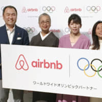 Yasuyuki Tanabe (left), chief of Airbnb Inc.'s Japan unit, and three-time Olympic wrestling gold medalist Saori Yoshida (second from right) pose during a news conference in Tokyo on Tuesday. | KYODO