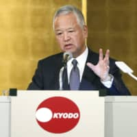 Akira Amari makes a speech at a meeting hosted by Kyodo News in Tokyo on Monday. | KYODO