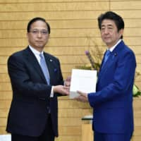 Board of Audit chief Yuji Morita submits to Prime Minister Shinzo Abe an annual report on wasteful spending at the Prime Minister's Office on Friday. | KYODO
