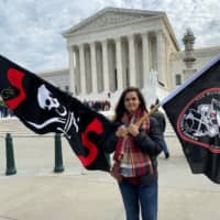 Christina Burnham holds pirate-themed flags in front of the Supreme Court in Washington NTuesday in support of her uncle, Frederick Allen, a filmmaker whose appeal in a copyright lawsuit over the use of his footage of Blackbeard's shipwreck is being heard by the justices. | REUTERS