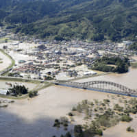 The town of Marumori, Miyagi Prefecture, is flooded on Oct. 13 after levees burst along the Abukuma River due to Typhoon Hagibis, which brought record-breaking rainfall and killed more than 90 people in the country. | KYODO