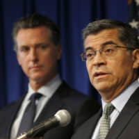 California Attorney General Xavier Becerra, flanked by Gov. Gavin Newsom, speaks during a news conference in Sacramento, California, in September. The California attorney general says he has been investigating Facebook's privacy practices since 2018. Becerra offered few details about the probe and said he was disclosing it only because his office was making a public court filing to force Facebook to answer its subpoenas, which Becerra said Facebook has failed to respond adequately to. | AP