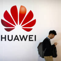 A man uses his smartphone as he stands near a billboard for Chinese technology firm Huawei at the PT Expo in Beijing last month. On Tuesday, Huawei announced it is paying its workers bonuses as thanks for helping the Chinese tech giant cope with U.S. sanctions threatening its smartphone and other businesses. | AP
