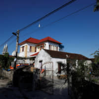 The newly built house of Bui Chung, who worked in Britain, is seen next to an older house at Do Thanh commune, in Nghe An province, Vietnam, Tuesday. | REUTERS