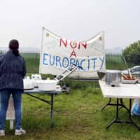 A woman stands at a collapsable table washing dishes during a rally to protest the construction of the EuropaCity Commercial and Leisure Mall project in Gonesse near Paris last May. France's president announced that the controversial Europacity project will be discarded, AFP reported Thursday. | AFP-JIJI