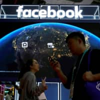 People walk by a Facebook sign at the second China International Import Expo in Shanghai on Wednesday. | REUTERS