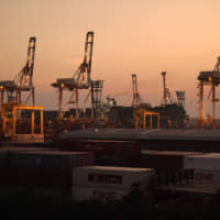 Stacked containers sit at a shipping terminal at dusk in Yokohama. The U.S.-China trade war and lackluster global demand have hurt Japanese exports and kept pressure on policymakers to ramp up stimulus in order to bolster a fragile recovery. | BLOOMBERG