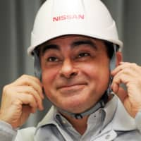 Nissan President and CEO Carlos Ghosn smiles as he puts on a helmet presented by factory workers while attending a ceremony to resume work on the assembly line at the company's engine plant in Iwaki, Fukushima Prefecture, in May 2011.  | AFP-JIJI