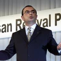 then-Nissan Motors President and CEO Carlos Ghosn gestures during a news conference on the progress of the carmaker's revival plan at a hotel in Tokyo in October 2000. | AFP-JIJI