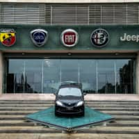 The logos of automobile companies (from left) Abarth, Lancia, Fiat, Alfa Romeo and Jeep are pictured at the entrance to the Fiat Chrysler Automobiles (FCA) at the Fiat Mirafiori car plant in Turin, Italy, in May. General Motors is suing Fiat Chrysler, alleging its rival benefitted from bribes to auto union officials that gave FCA an unfair benefit in labor talks, GM announced Wednesday. | AFP-JIJI