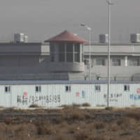 A guard tower and barbed wire fences are seen around a facility in the Kunshan Industrial Park in Artux in western China's Xinjiang region in December. | AP