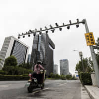 A scooter passes beneath surveillance cameras at a testing station near the headquarters of Hangzhou Hikvision Digital Technology Co. in Hangzhou, China. | BLOOMBERG