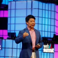 Huawei's rotating chairman, Guo Ping, speaks during the Web Summit in Lisbon Monday. | REUTERS