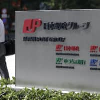 A pedestrian walks past a sign showing logos of Japan Post Group companies in Tokyo in July. Japan Post Holdings Co. said Thursday its group revenue in the April-September half dropped 4.8 percent from a year earlier to ¥5.96 trillion. | BLOOMBERG