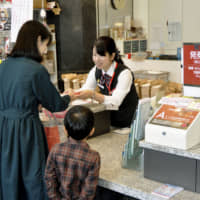 A customer receives assistance at a post office in central Tokyo on Nov. 1.   KYODO
