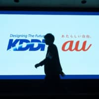 KDDI Corp.'s logo is projected onto a screen before a news conference in April 2018 in Tokyo. | BLOOMBERG