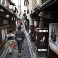 A couple wearing rental kimono walk through the Pontocho dining area of Kyoto. The tourist destination is considering the sale of debt to finance environmental, social and governance projects, according to its mayor. | BLOOMBERG