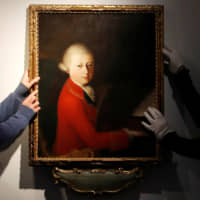 Workers install a portrait due to be sold at auction by Christie's that depicts composer Wolfgang Amadeus Mozart as a teenager, painted in January 1770, and attributed to Veronese master Gaimbettino Cignaroli, in Paris Tuesday. | REUTERS